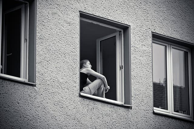 Pige i vindue kigger mod himmelen